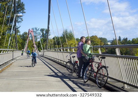 A couple in their forties take a break on the bike bridge overlooking Alton Baker Park in Eugene Oregon on a beautiful sunny day. - stock photo