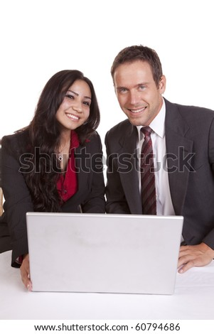 A couple is sitting at a laptop computer smiling and looking. - stock photo