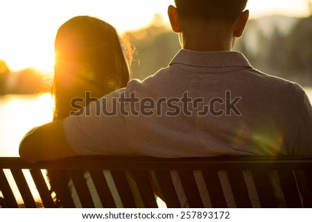 A couple is sitting on a bench contemplating life during a dramatic warm sunset. - stock photo