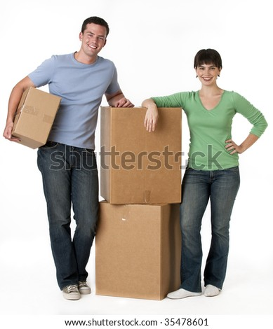 A couple is standing next to moving boxes and they are smiling at the camera.  Vertically framed shot.