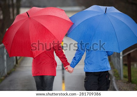 A couple is walking hand in hand through the rain with umbrellas and rain cloth.