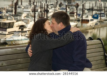 A couple kissing on a wooden bench in front of a boat marina. - stock photo