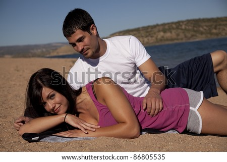 A couple laying on the beach being close. - stock photo