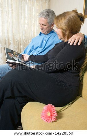 A couple looking at a book of pictures together, reminiscing - vertically framed - stock photo