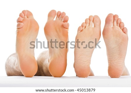 A couple lying next to each-other with naked feet.