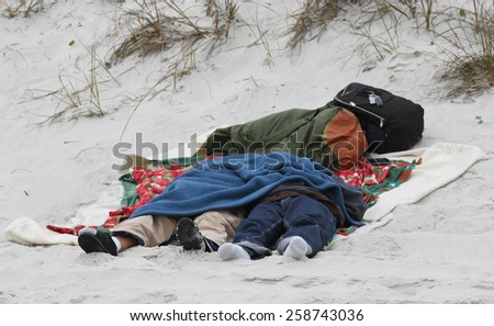 A couple of beach bums catching a nap on the shore - stock photo
