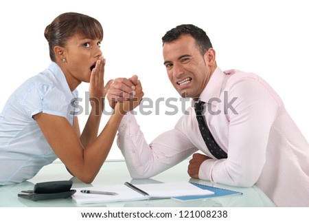 A couple of businesspeople arm wrestling.