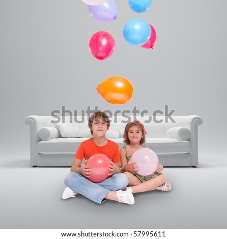 A couple of children with a white sofa and colorful balloons - stock photo