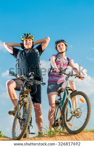 a couple of cyclists in helmets on bikes posing
