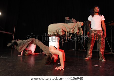 A couple of female and one male freestyle hip-hop dancers during dance training session on stage. Lit with spotlights