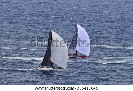 A couple of leading yachts racing open ocean during Sydney Hobart yacht race close up speeding under fresh wind with full sails