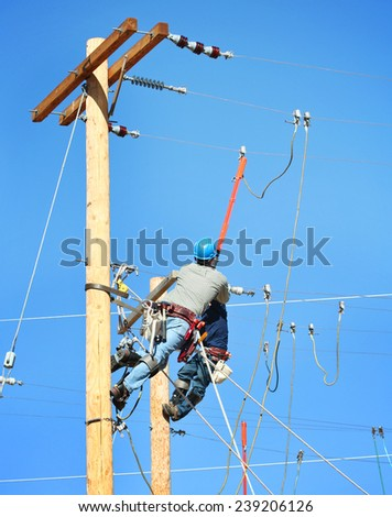 a couple of linemen working on power lines - stock photo