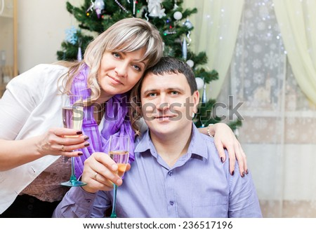 a couple of middle age with glasses of champagne at the Christmas tree - stock photo