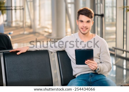 A couple of minutes till flight. Portrait of handsome man in casual wear speaking over his mobile phone and looking at his watch while sitting in the hall of the airport
