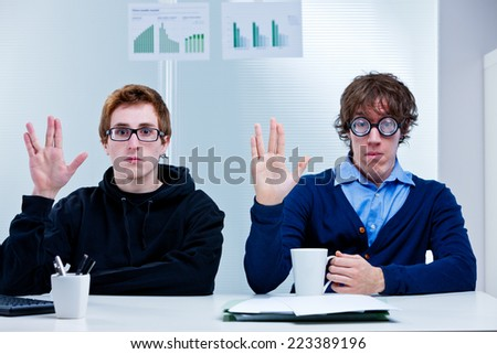 a couple of nerd office workers showing a very popular science fiction salutation - stock photo