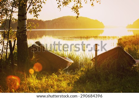 A couple of old rowing boats in the sunset. They are laying by the birch. Image has a vintage effect. - stock photo