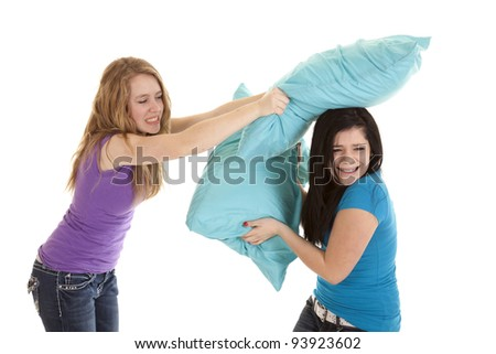 a couple of teenage girls having a pillow fight, laughing and having some fun. - stock photo