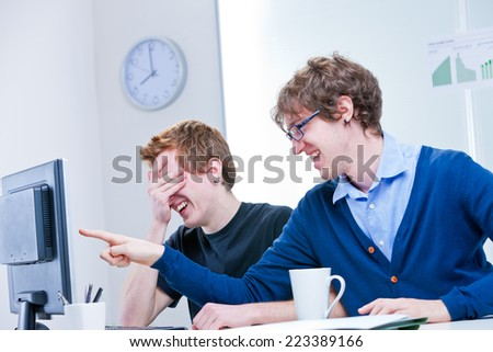 a couple of two young office workers laugh at what is happening on the screen - stock photo