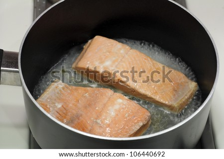 A couple of wild salmon fillets being cooked in a small amount of water in a saucepan on a stove top. - stock photo