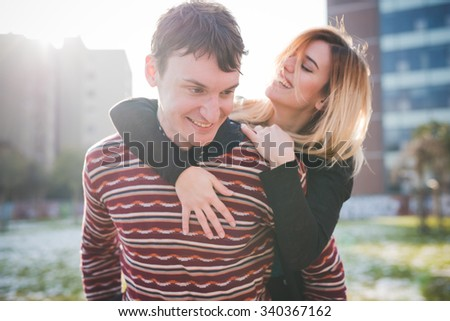 A couple of young lovers embraced, smiling and having fun in the city. He is looking downward and she is looking at him - love, fun, carefree concept - stock photo