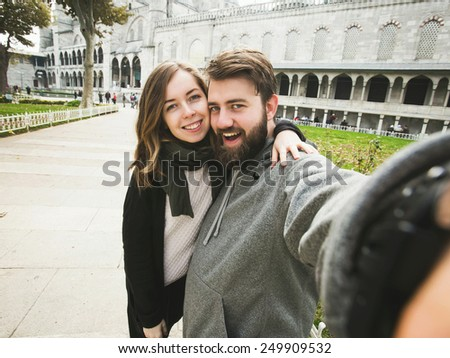 A couple of young tourists takes selfie portrait in front of Blue Mosque in Istanbul, Turkey - stock photo