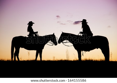 A couple on horseback at sunset - stock photo