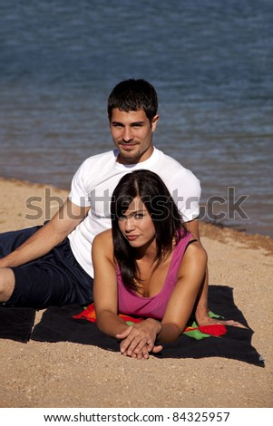 a couple on the beach relaxing together. - stock photo