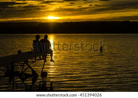 A couple on the end of the pier at sunset at Struthers Lake, Saskatchewan