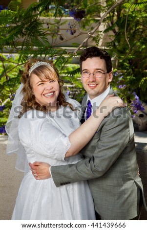 A couple on their wedding day.  They have great, big, just married smiles.