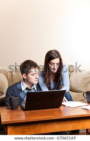 A couple paying bills by using online banking at home - stock photo