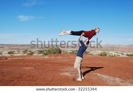 A couple performing a lift in the desert of Moab, UT. - stock photo