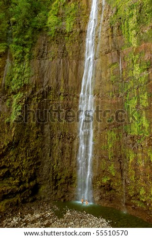 A couple plays in Waimoku Falls - a waterfall in Haleakala National Park, Maui, Hawaii - stock photo