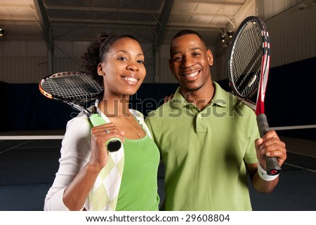 a couple posing next to a tennis court - stock photo