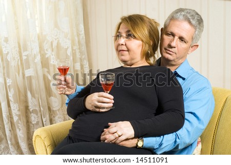 A couple relaxing with wine glasses.  The female figure is seated on the male's lap.  She is smiling. Horizontally framed shot. - stock photo