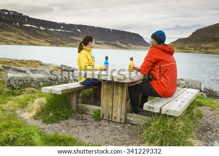 A couple resting close to a beautiful lake