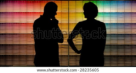 A couple selecting paint samples from a paint store color chart - stock photo