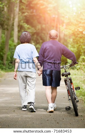 A couple senior asian talking while walking and exercising at a park