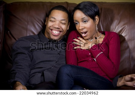 A couple show expression during a romantic moment on tv