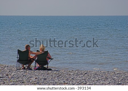 A couple sit on deckchairs enjoying the beach - stock photo
