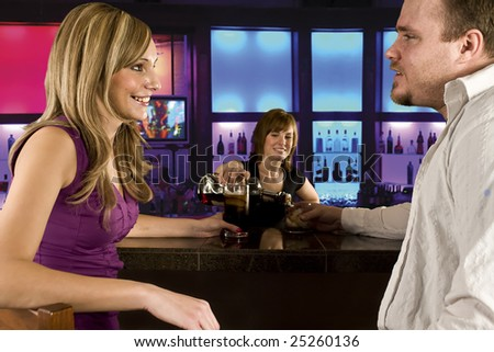 A couple sitting at bar with bar tender pouring a drink - stock photo