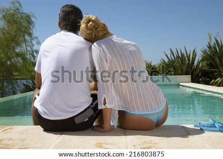 A couple sitting by the pool.