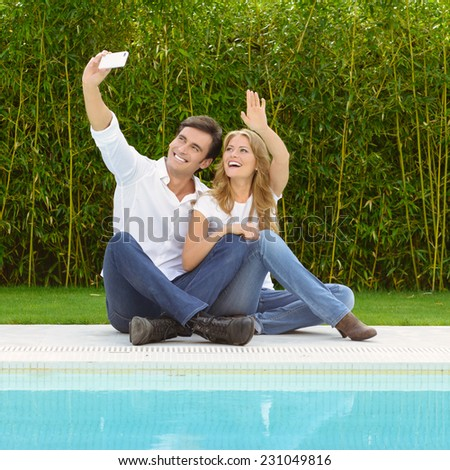 A couple sitting by the pool taking a selfie with the smart phone - stock photo