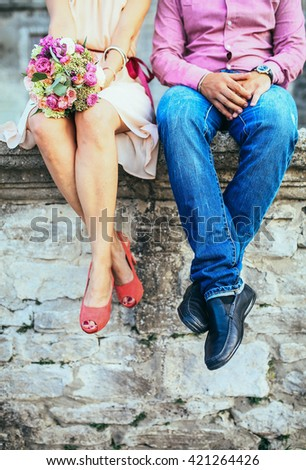 A couple sitting on a stone wall in jeans wearing shoes. Shot from the legs down. - stock photo
