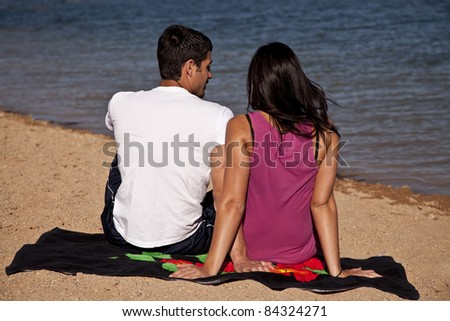 A couple sitting on the beach on their towel with their backs to the camera. - stock photo