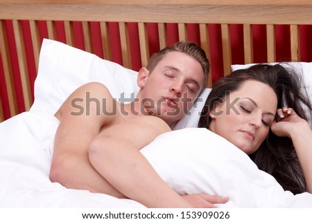 A couple sleeping in bed cuddles up together - stock photo