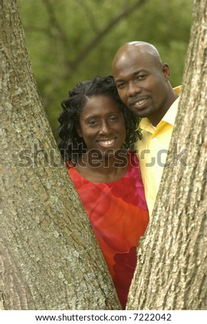 a couple smiling by a large tree
