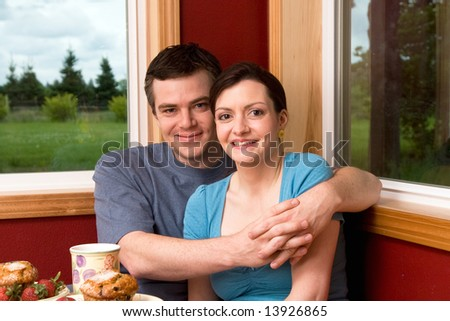 A couple smiling by large windows at home.  The man is hugging the woman.  Horizontally framed shot.
