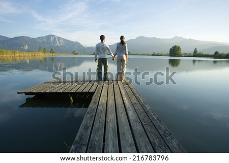 A couple standing at the end of a pier. - stock photo