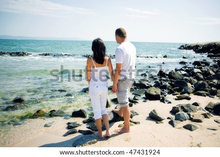 A couple standing on beach - stock photo
