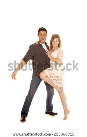 A couple standing together her hanging on him with one leg up. - stock photo